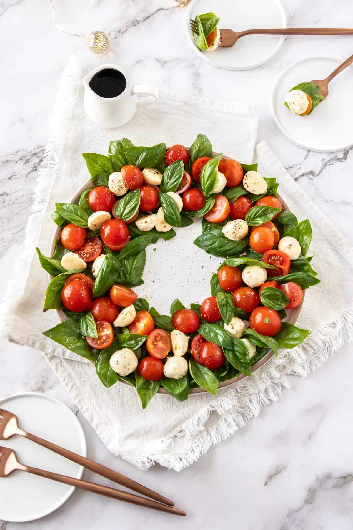 Caprese salad in a wreath circle, on a white plate, sitting on a white cloth, with a jug of balsamic glaze in the background.