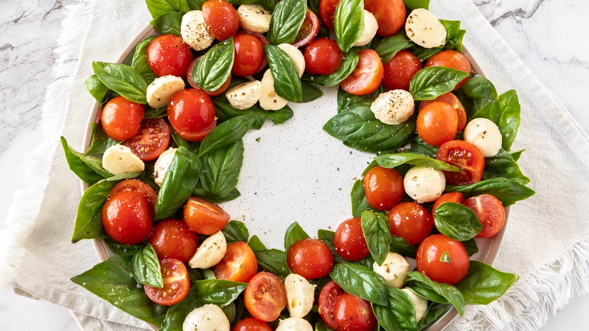Caprese salad in a wreath circle, on a white plate, sitting on a white cloth.