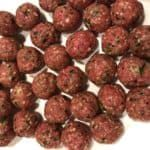 Meatballs that have been rolled out and are ready to bake.