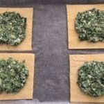 Four puff pastry squares topped with a spinach and feta mixture.