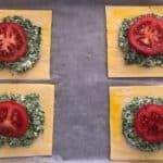 Four puff pastry squared topped with spinach and feta and a slice of tomato, brushed with egg around the edges.