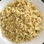Cooked quinoa in white bowl cooling down.