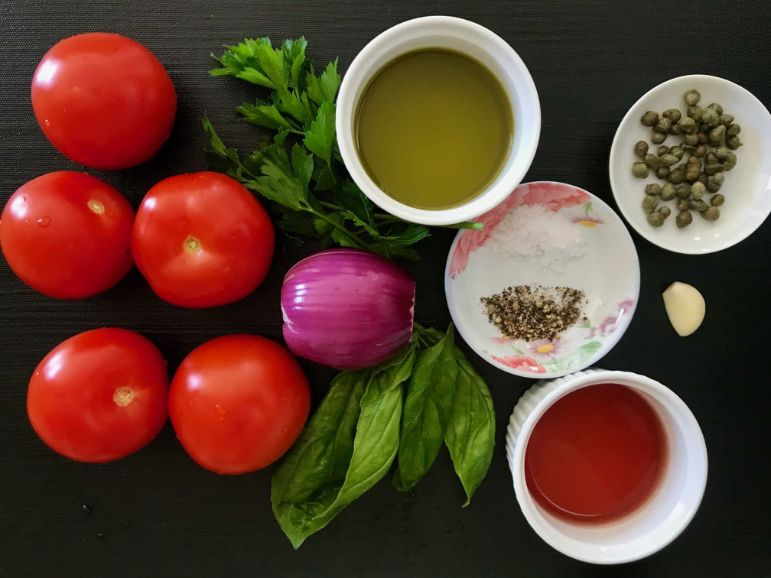 Black place mat with all of the ingredients for the Marinated Tomato Salad.