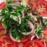 Slices of tomatoes, red onions and herbs in a white bowl.