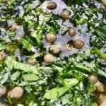 Bowl of dressing with herbs and capers.