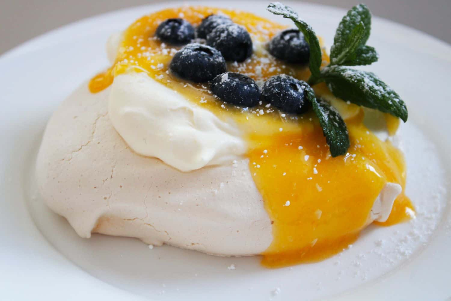 One Meringue on a white plate, topped with cream, lemon curd and blueberries. Garnished with a sprig of mint.