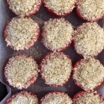 6 tomatoes cut in half, filled with breadcrumb mixture on a baking paper lined tray, ready for the oven.