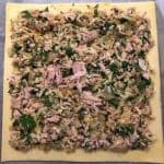 Sheet of puff pastry on baking paper with tuna mixture evenly spread out.