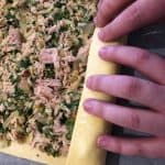 Sheet of puff pastry with tuna mixture being rolled.