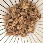 Walnuts sitting in white colander.