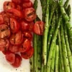 White plate with grilled tomatoes on the left and grilled asparagus on the right.
