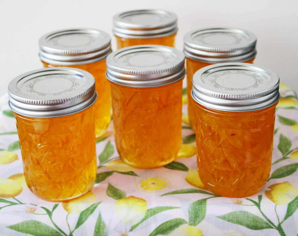 Six jars of Lemon Marmalade on a lemon cloth.