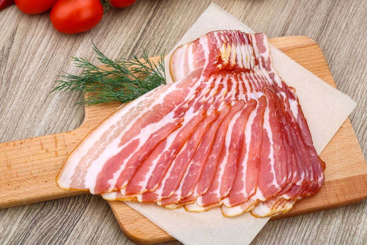 Rashers of bacon on a wooden board.