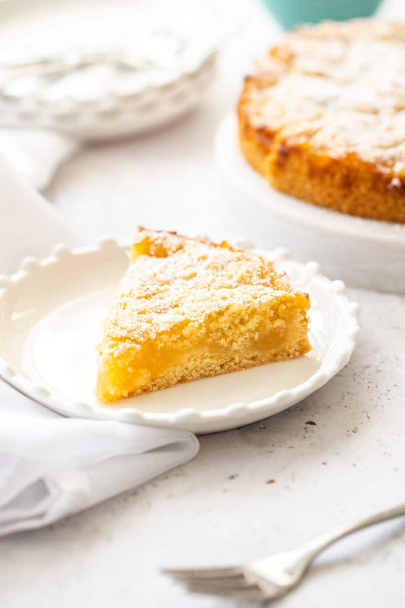 up close shot of a slice of lemon cake, sitting on a white cloth, with the rest of the cake in the background.