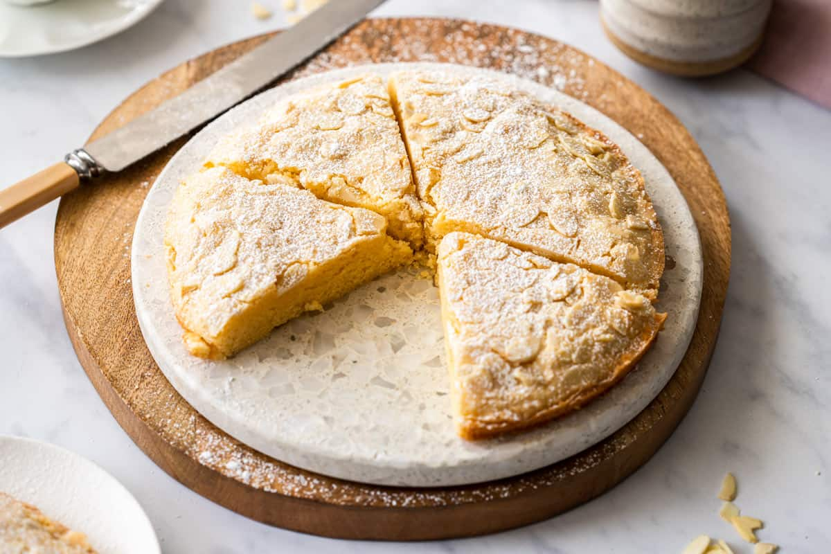 Almond cake, on round plate sitting on a round wooden board. A piece missing, which sits down the left bottom corner.