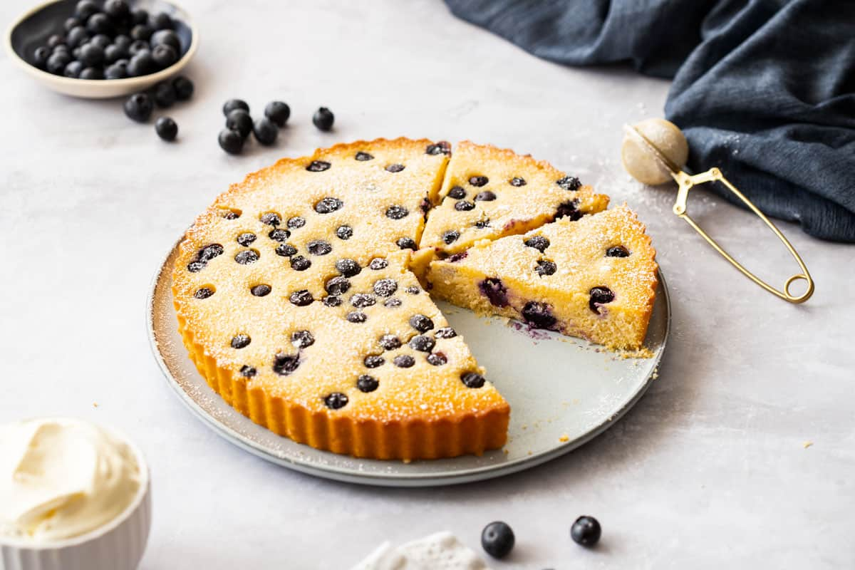 Blueberry Cake with one slice removed on grey platter.