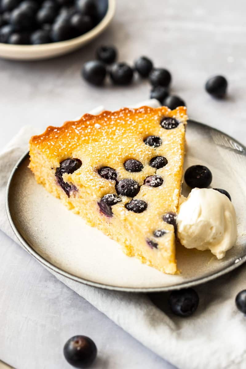 Slice of Gluten-Free Blueberry Cake on grey plate with a dollop of cream.