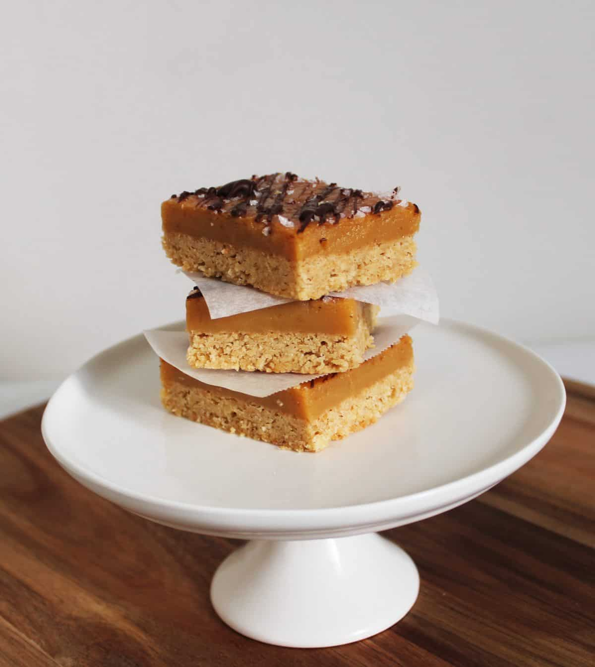 Three pieces of caramel slice stacked on a round white plate sitting on a wooden board.