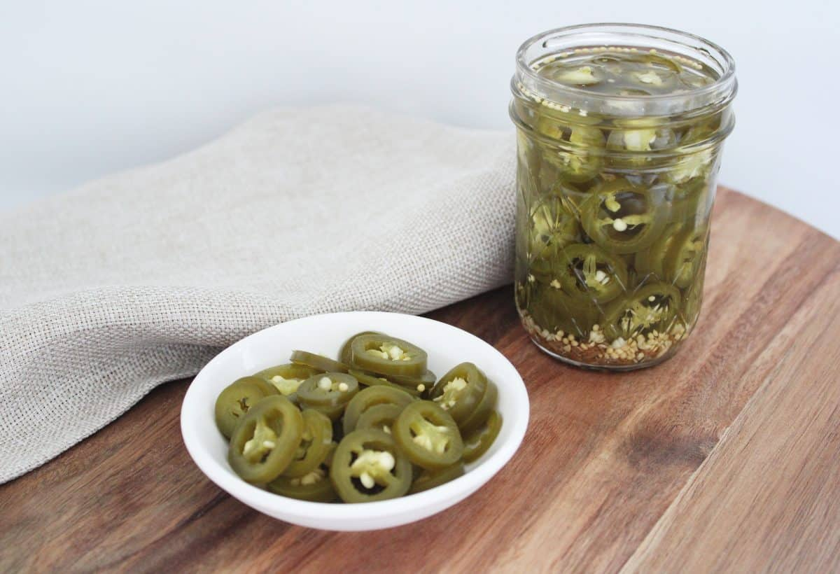 small white round dish of jalapeno and a jar of jalapeno, on a wooden board, with a pale brown napkin.