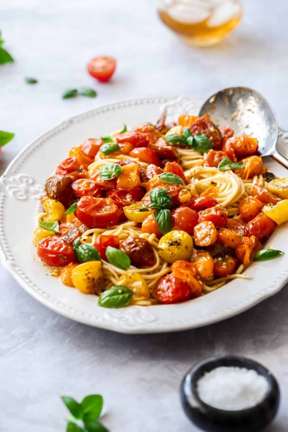 large white platter of pasta, topped with roasted tomato sauce and garnished with basil leaves. silver spoon on edge of dish.