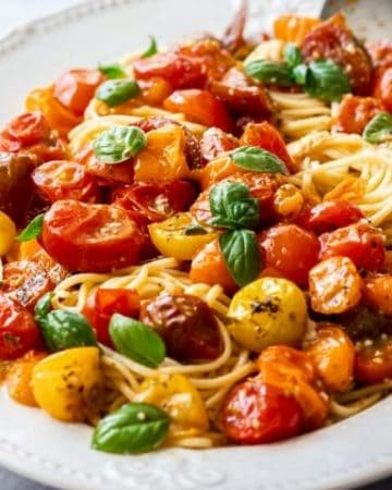 large white platter with pasta, topped with roasted tomatoes and fresh basil leaves.