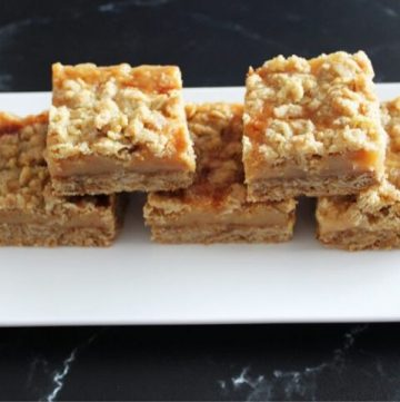 five caramel crumb bars on a white plate, sitting on a black benchtop.