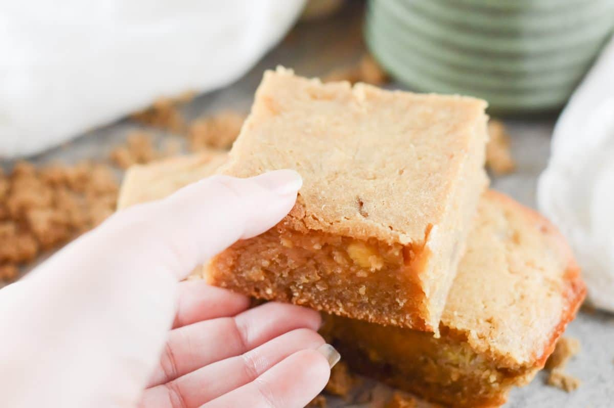 hand holding up one banana blondie. another two blondies in photo on a grey board. some crumbs around, and in the background a green mug and white cloth.