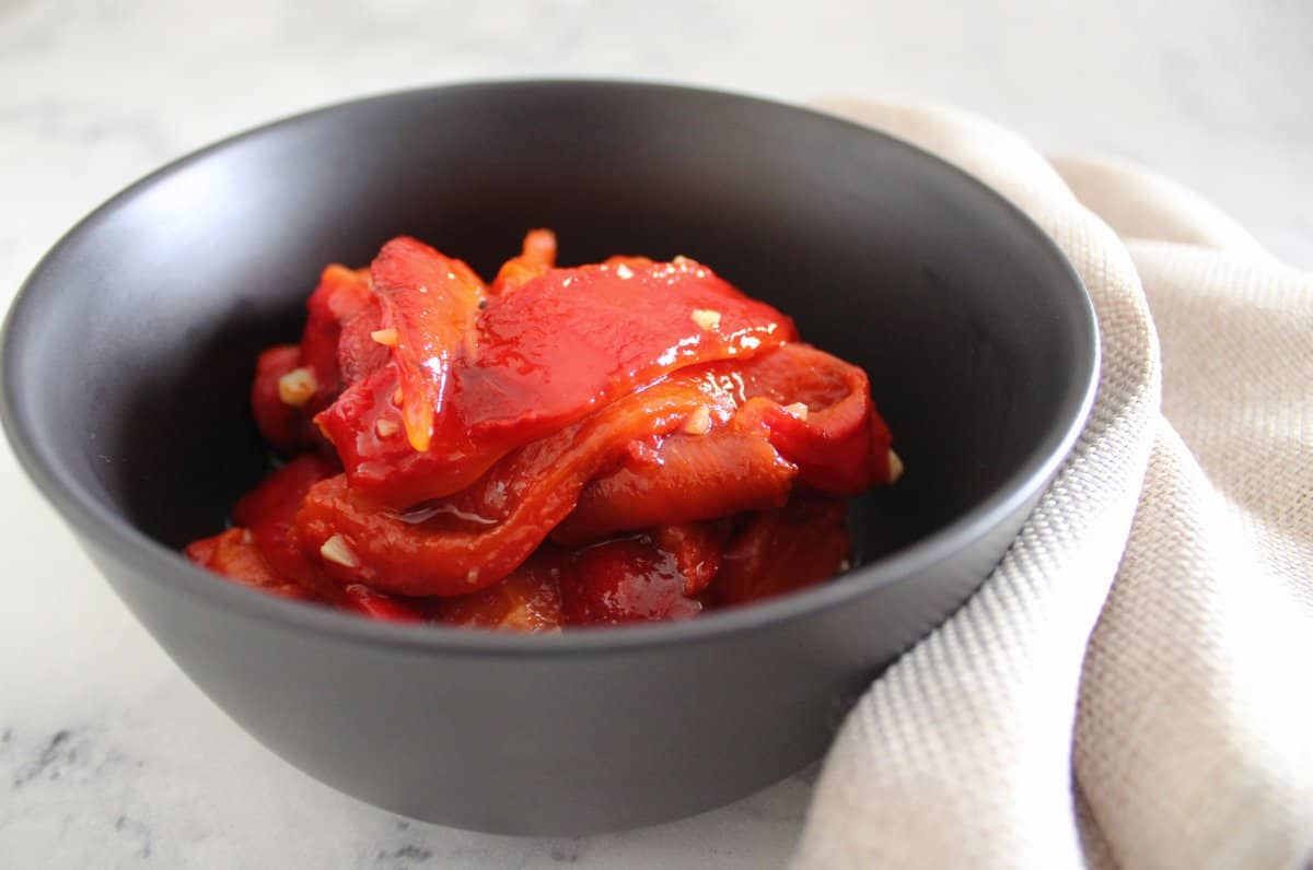 black bowl with roasted capsicums, with a beige napkin. Sitting on a marble benchtop.
