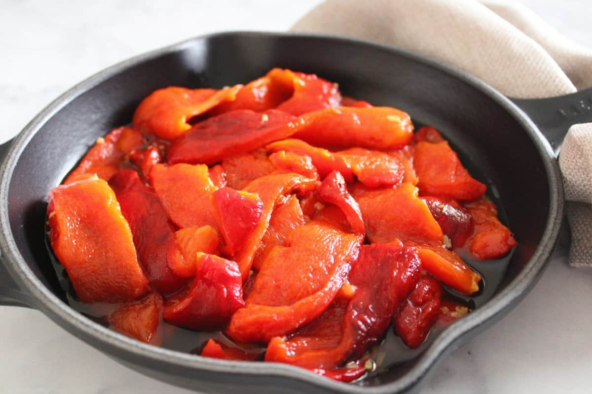 Black skillet with roasted peppers, with a beige napkin on a marble background.