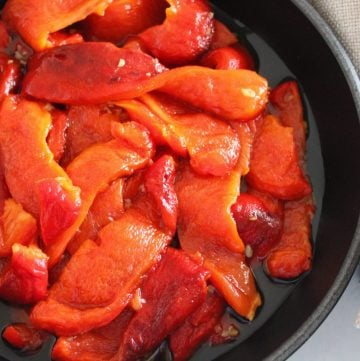 Black skillet with roasted peppers, with a beige napkin.
