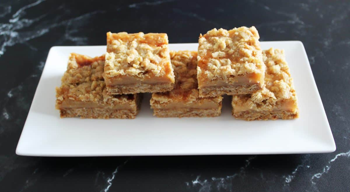 Five caramel crumb bars on a white plate on a black benchtop.