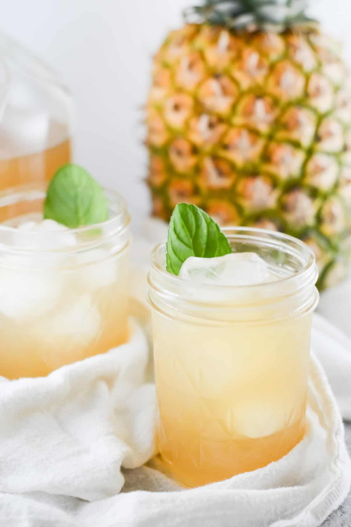 two glasses of iced tea with a pineapple in the background