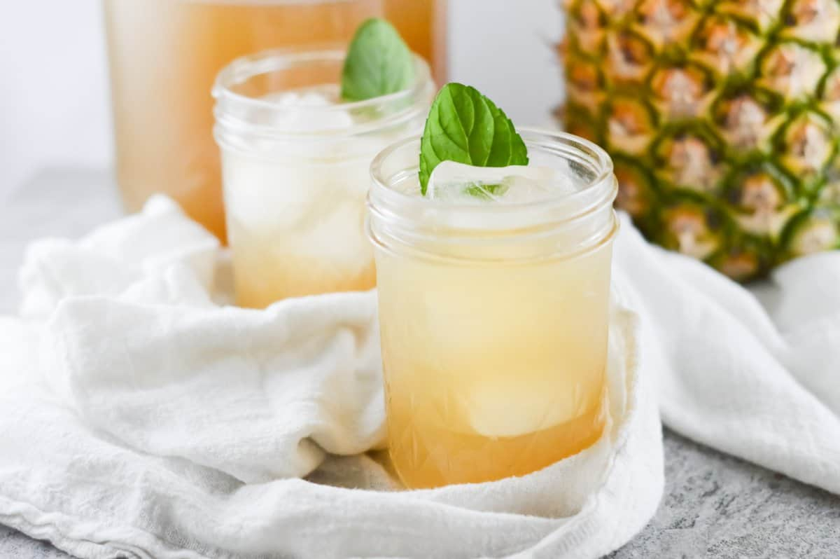 two glasses of iced tea on a white towel with a pitcher and pineapple in the background.