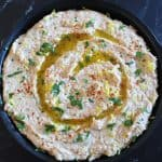 Black dish of tuna and white bean dip on black marble background.