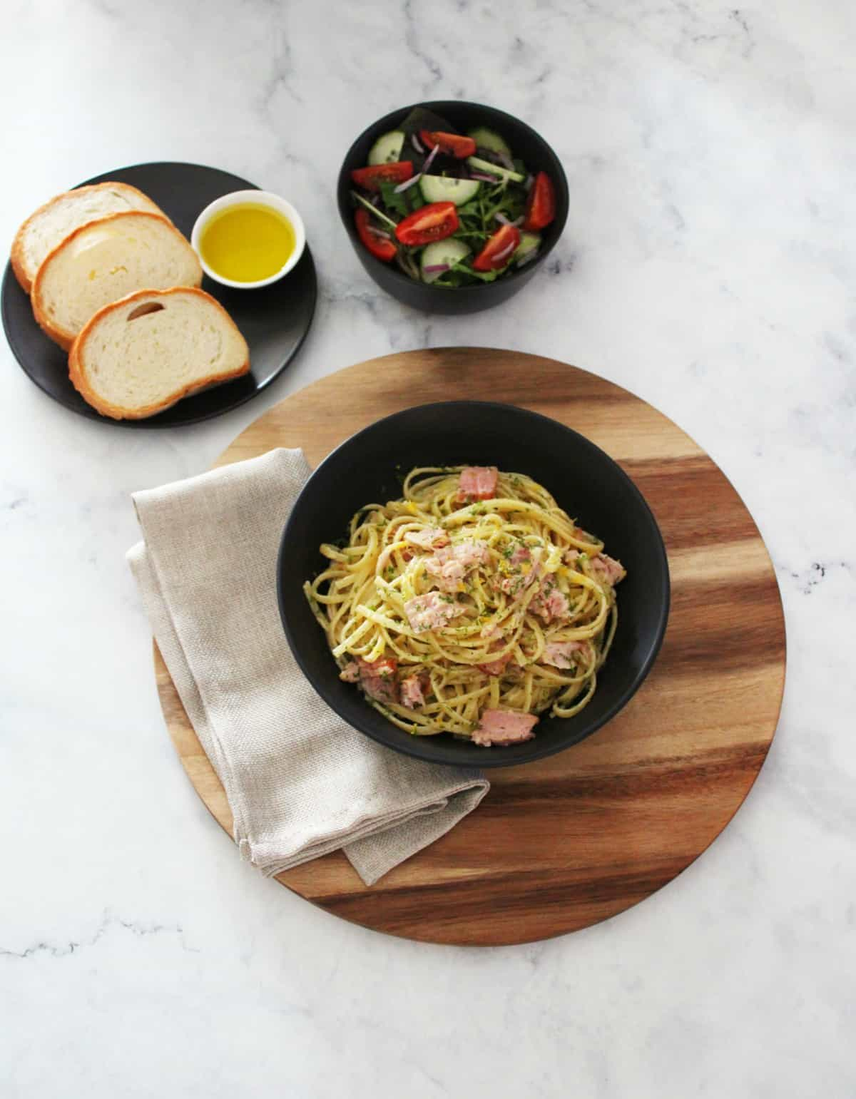overhead shot of creamy tuna pasta in black bowl on wooden board, with a plate of bread and a bowl of salad.