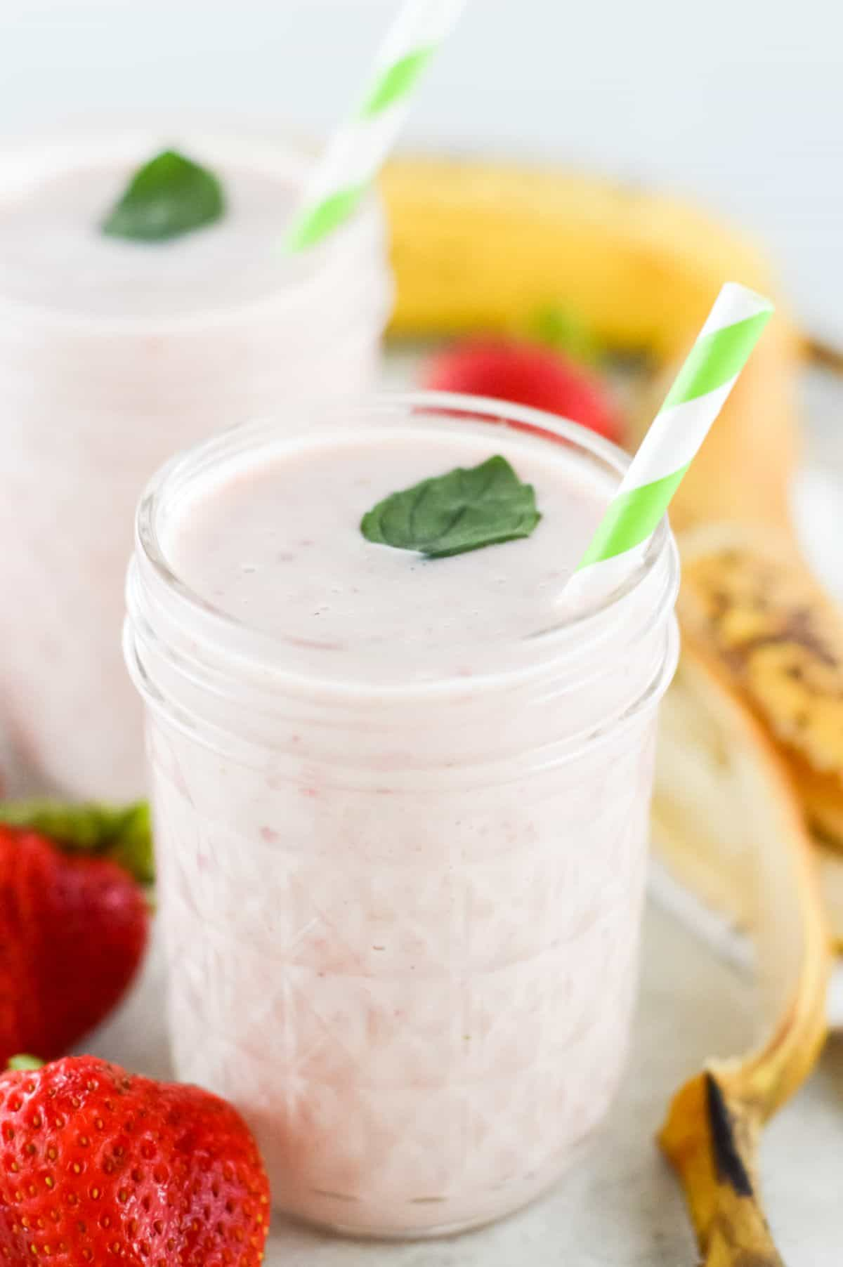 Two glasses of smoothie, on a white bench, with some strawberries and banana peel and a white tea towel around the glass.