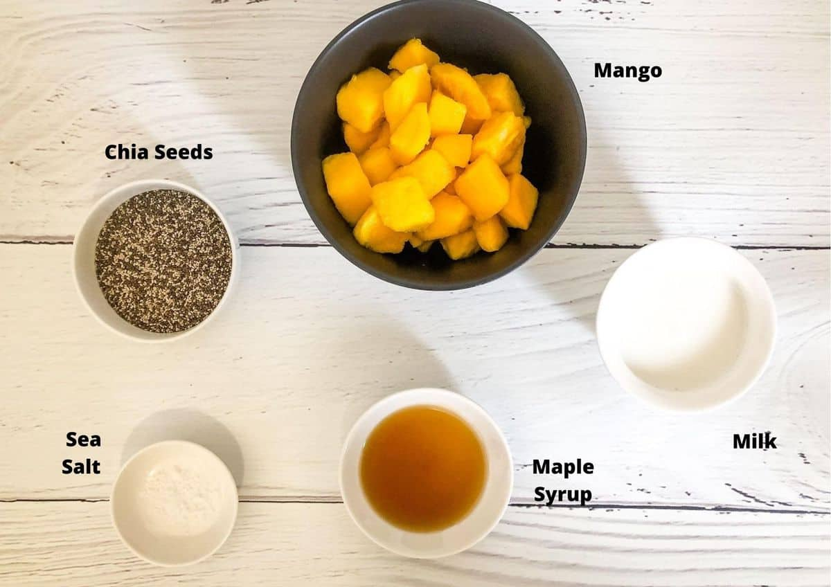 Ingredients in this recipe for chia pudding on a white timber background.