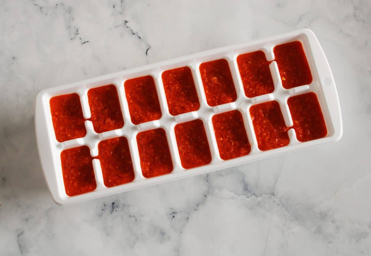 Ice cube tray, full of red chilli paste, on a marble background.