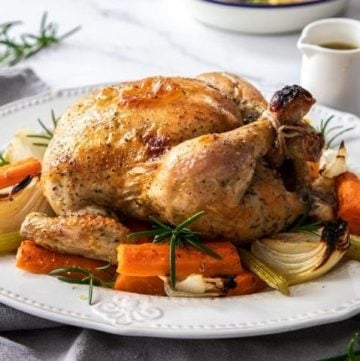 Roast Chicken on a white platter, surrounded by carrot, celery and onion. A sprig of rosemary and white jug of gravy are in the background.
