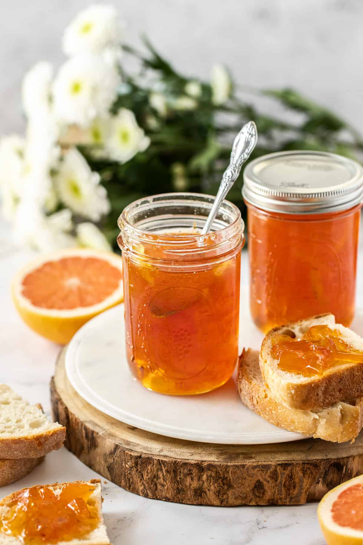 two jars of marmalade on a round board, one with a spoon in it, and some bread and grapefruit surrounding the board.