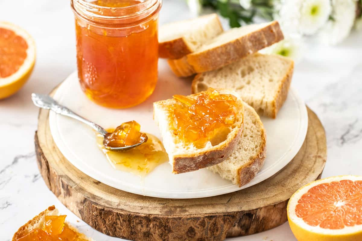 two jars of marmalade on a round board, a spoon of marmalade on the board, and some bread and grapefruit surrounding the board.