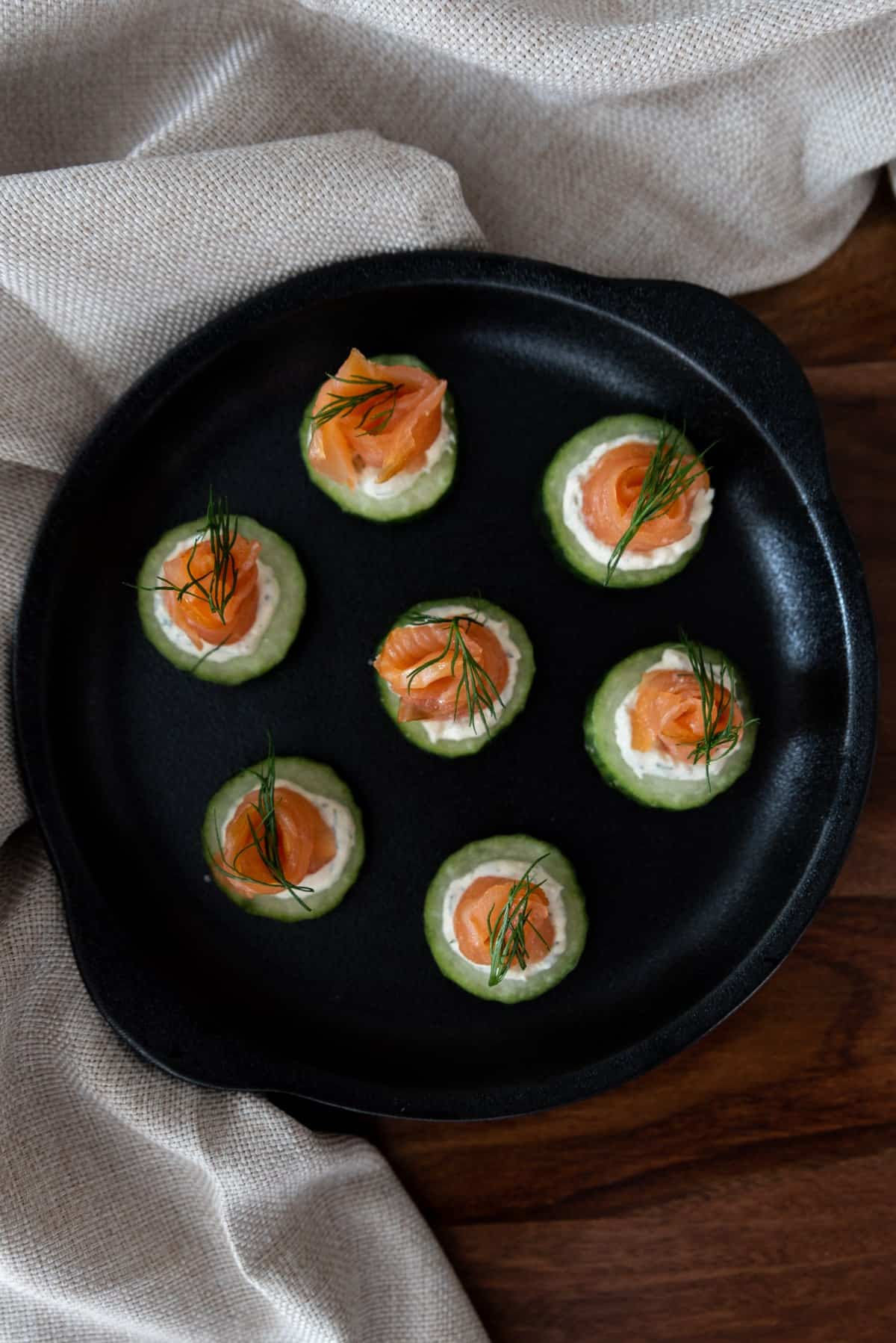 cucumber bites in a round black cast iron dish, sitting on a timber table, with a beige napkin around the edge.