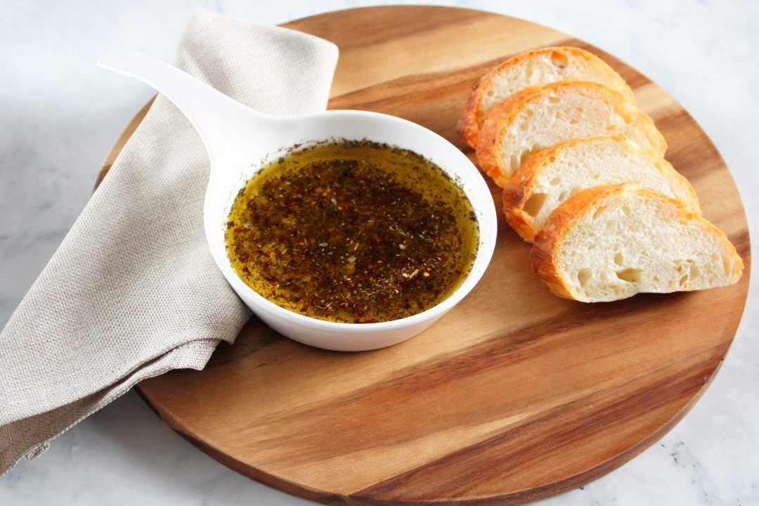 On a round wooden board, a beige napkin, round white dish of dipping oil and four slices of bread.