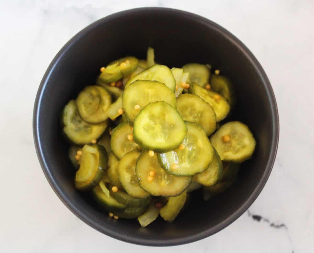 Round black bowl with pickles, set on a white marble background.