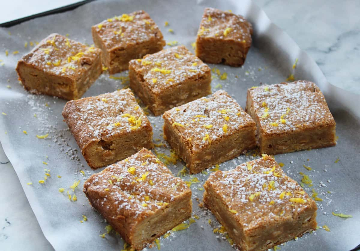 baking tray with blondies spread out on some baking paper. they have been dusted in icing sugar and lemon zest.