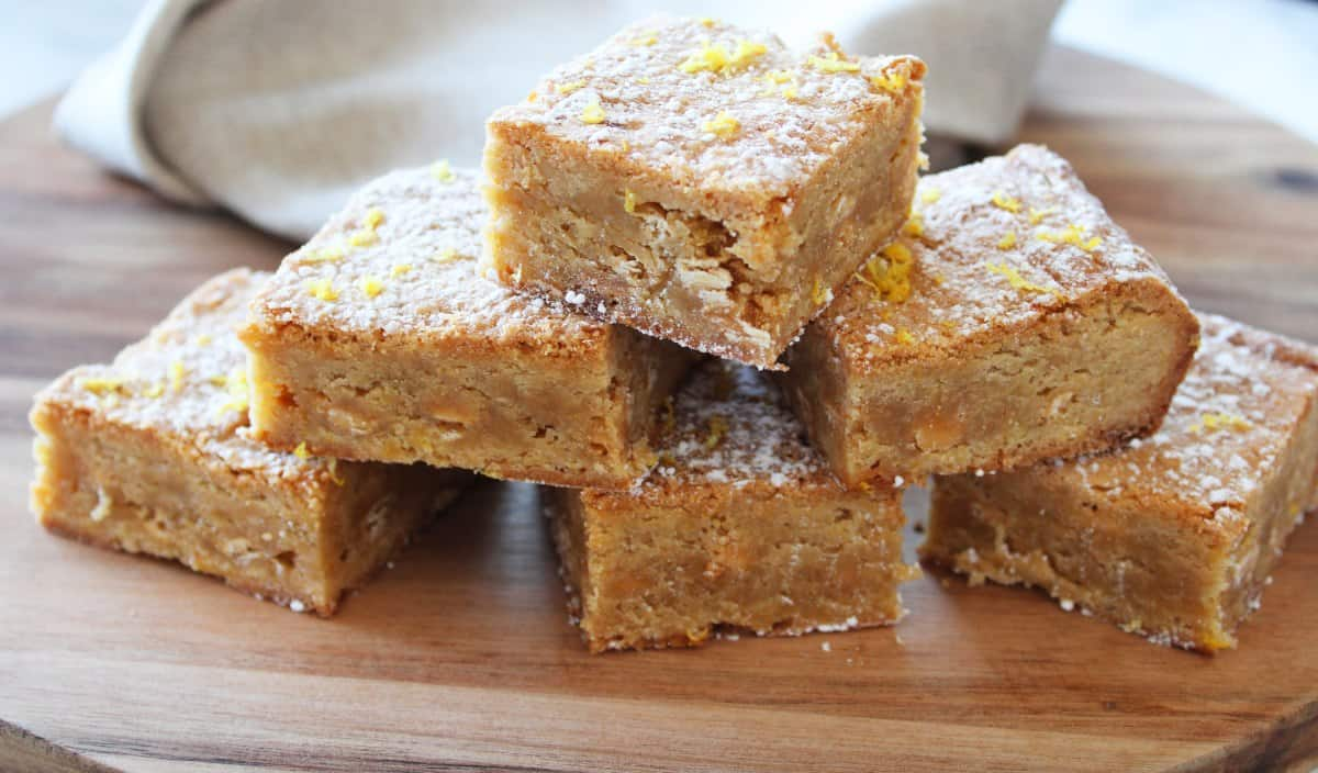 blondies stacked on round wooden board, with a beige napkin in the background.