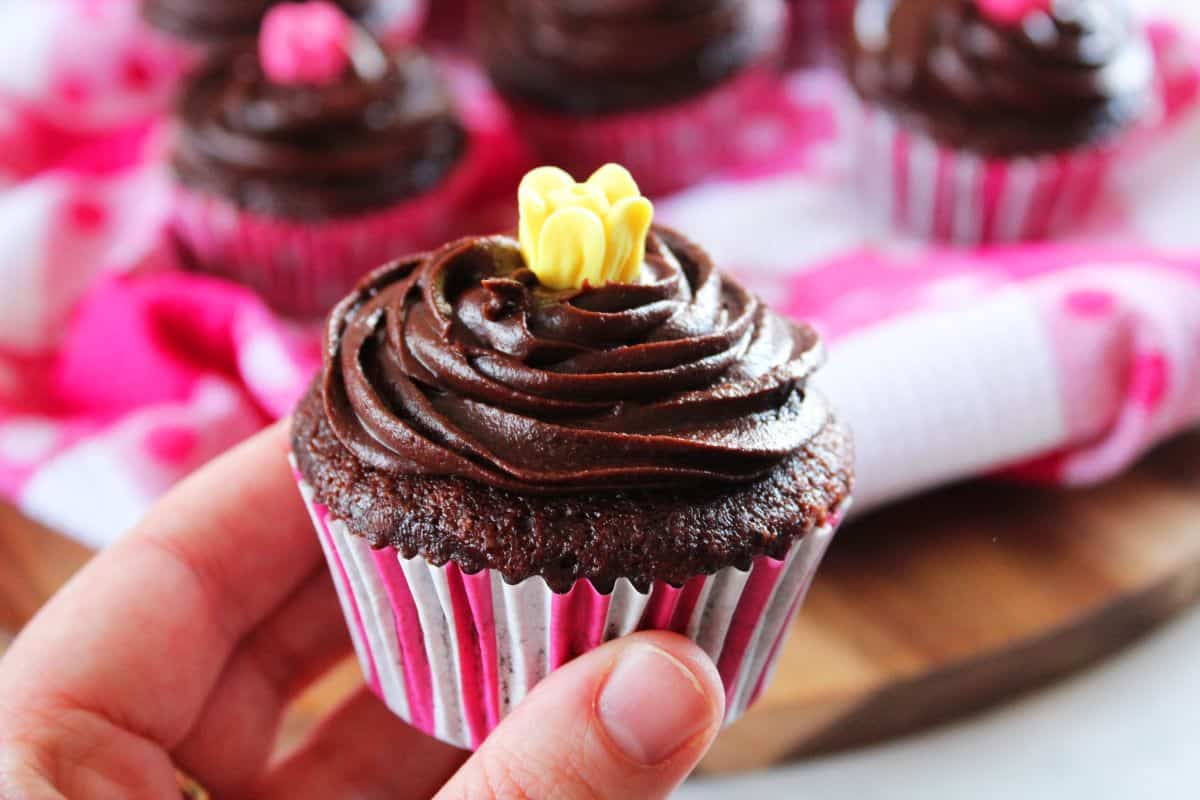 A hand holding a cupcake up close, with cupcakes in the background sitting on a pink and white spotty tea towel.