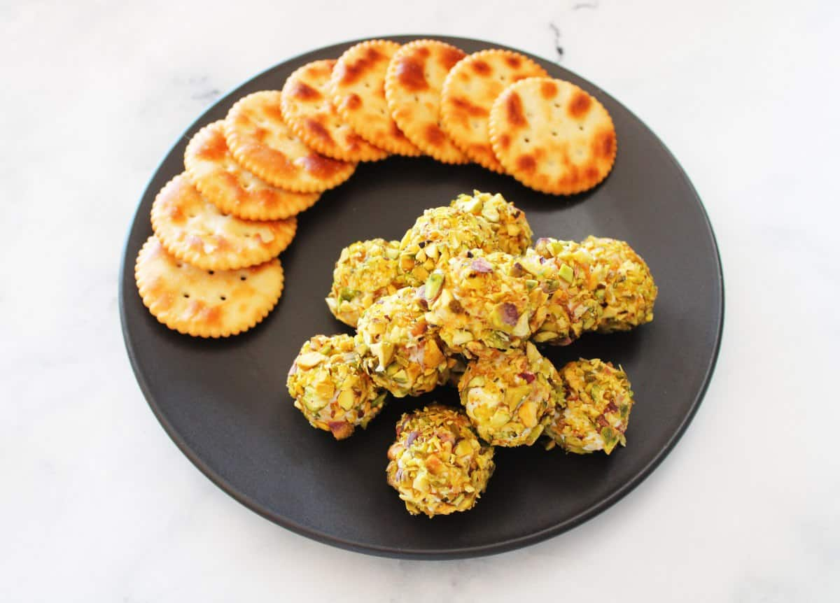overhead shot of cheese bites on round black plate, with crackers, sitting on a white marble bench.