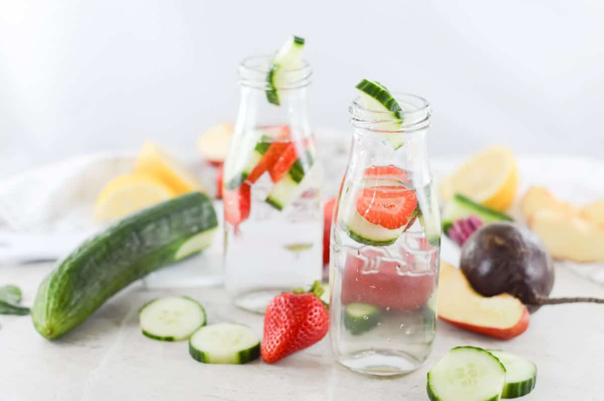 Two glass bottles on infused water (with strawberry and cucumber) on a board, surrounded by fruit and vegetables.