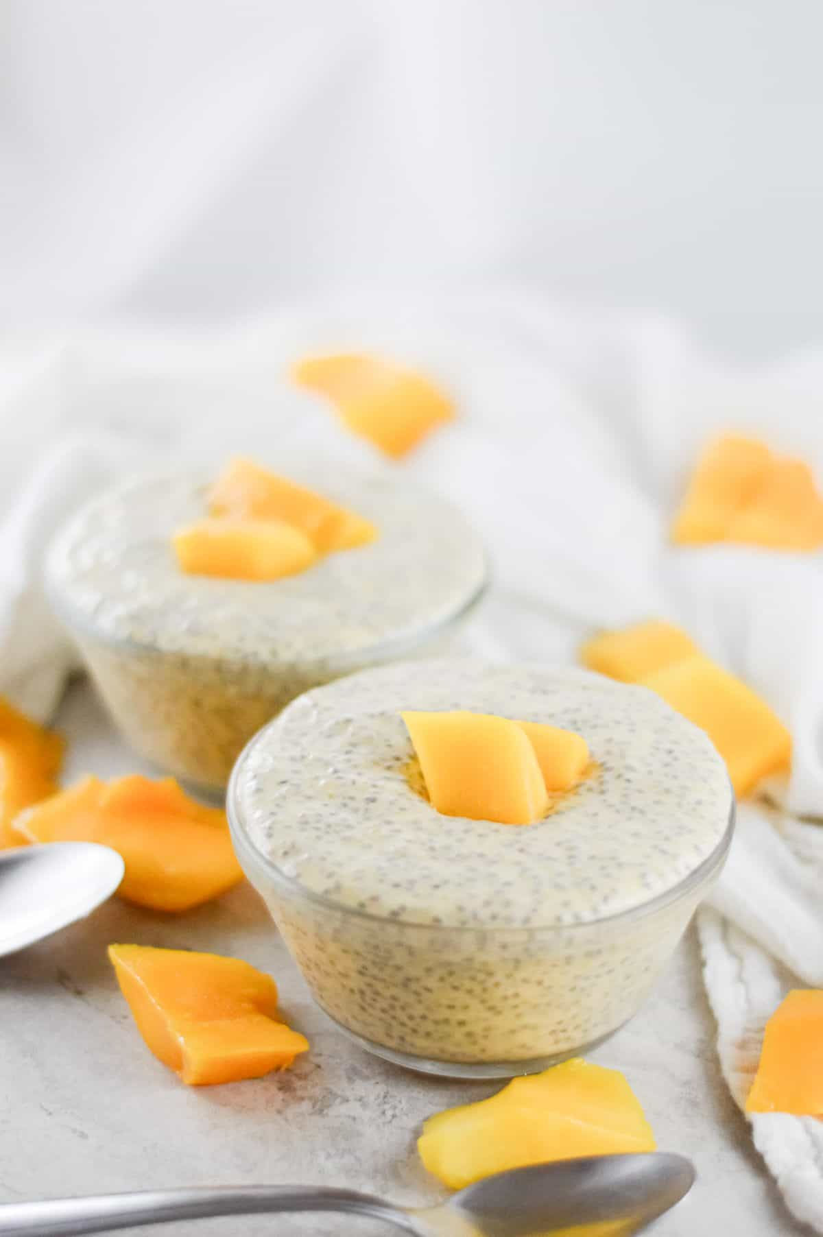 On a white bench, two bowls of chia pudding, garnished with mango sit. Mango pieces scattered around the bowls, and there are two silver spoon on the left. A white cloth in the background.